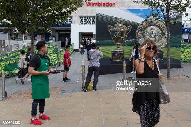 A Starbucks employee hands out the last free iced coffee to passersby near a large hoarding showing the Mens' and Ladies' trophies outside the...
