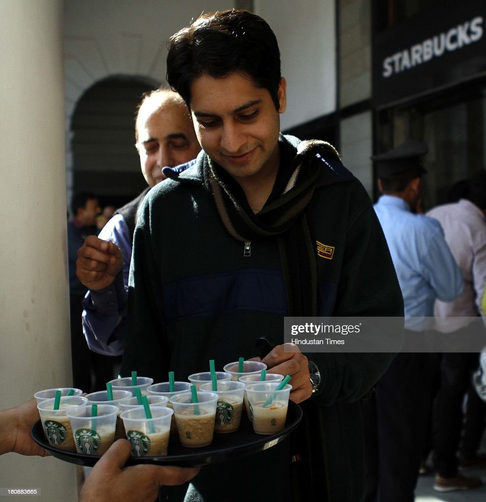 Starbucks employee offers coffee shots of different flavors to Coffee lovers who are waiting in long queue to get inside newly opened Starbucks outlet at Connaught Place on February 7, 2013 in new Delhi, India.