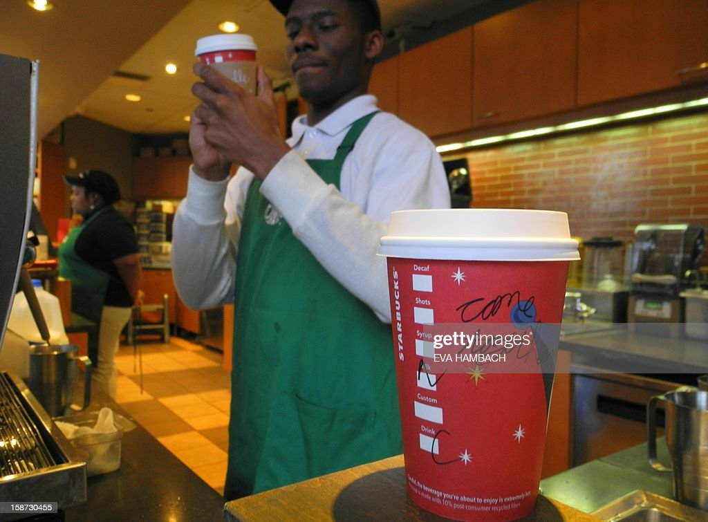 A Starbucks employee writes a message on a cup of freshly brewed coffee at a local store in Washington, DC on December 26, 2012. Starbucks stirred the political pot Wednesday by urging its baristas to write 'come together' on its cups as a way to pressure US lawmakers to compromise on a deal to avert a year-end fiscal crisis. Starbucks chief executive Howard Schultz said the American coffee giant was recommending its first-ever message on the side of tall, grande and venti (small, medium and large) drinks sold at its Washington stores as a way to help break the capital's gridlock on the so-called 'fiscal cliff.' Lawmakers and the White House have less than a week to work out a deal aimed at preventing tax hikes from hitting all Americans and a series of deep, mandated spending cuts from kicking in beginning January 1. AFP PHOTO/Eva HAMBACH