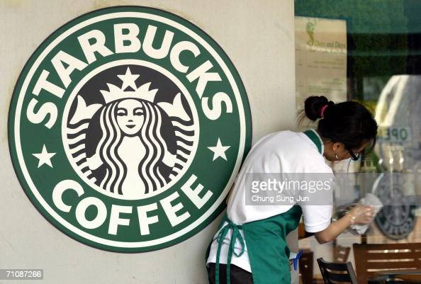 Starbucks worker cleans the window next to a company logo at a coffee store on May 31 2006 in Seoul South Korea The National Tax Service has launched...