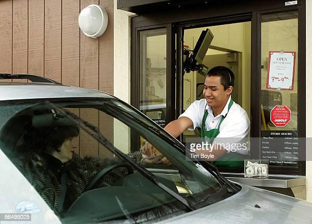 Starbucks worker Freddie Arteaga assists a customer with her drink order at a Starbucks drivethru December 28 2005 in Wheeling Illinois Starbucks is...