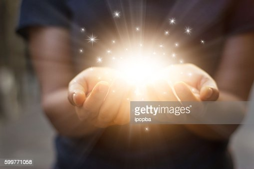 Stardust and magic in woman hands on dark background : Foto stock