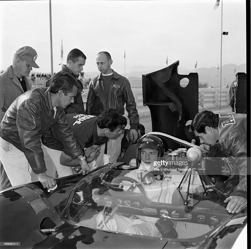 Stardust Grand Prix CanAm Las Vegas AAR founder and driver Dan Gurney sits in his Lola T70 as team mechanics and crew member prep him fot the race