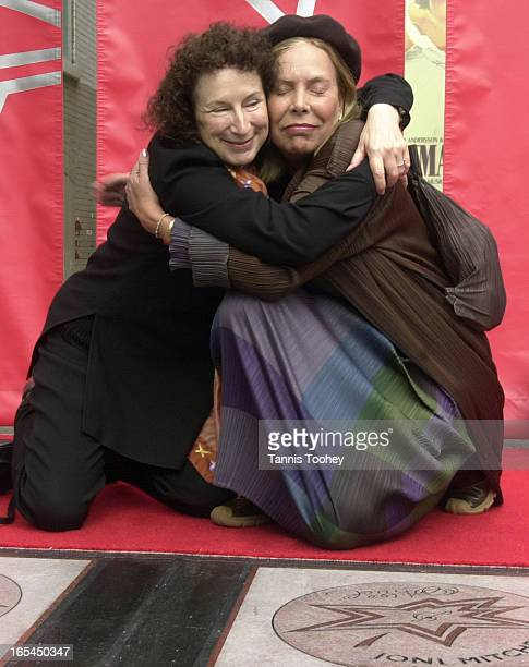 Newly inducted walk of fame stars Margaret Atwood and Joni Mitchell embrace after unveiling their stars on the walk of fame on King Street West...