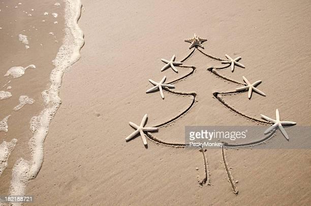 Étoile de Noël arbre de Noël dessin dans le sable et vagues