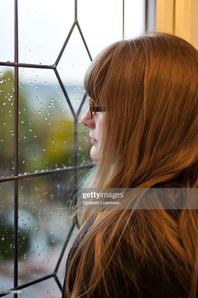Staring from her window : Stock Photo
