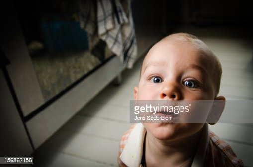 Staring nine month old boy in kitchen : Stock Photo