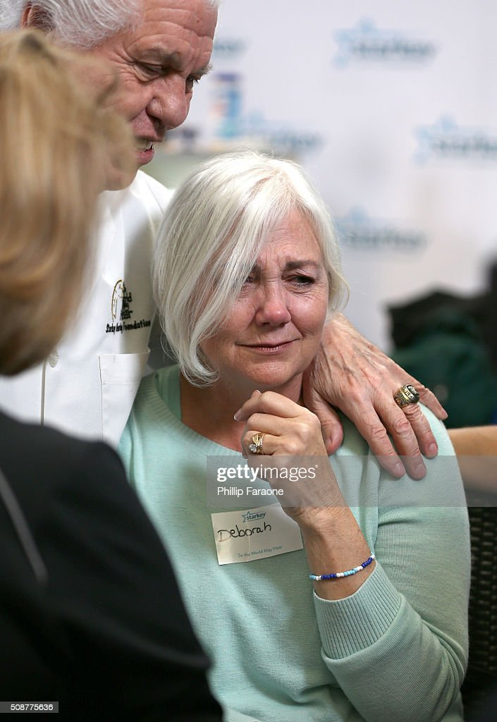Dr. Bill Austin attends to patient Deborah after she received her hearing aid during the Starkey Hearing Foundation hearing mission during Super Bowl weekend 2016 at San Francisco State University on February 6, 2016 in San Francisco, California.