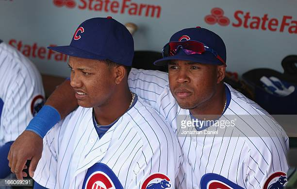 Starlin Castro and Luis Valbuena of the Chicago Cubs wait in the dugout for player introductions before the Opening Day game against the Milwaukee...