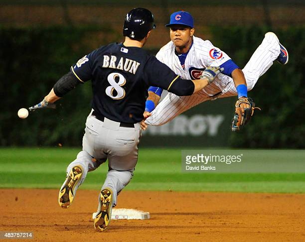 Starlin Castro of the Chicago Cubs can't handle a errant throw as Ryan Braun of the Milwaukee Brewers is safe at second base during the ninth inning...
