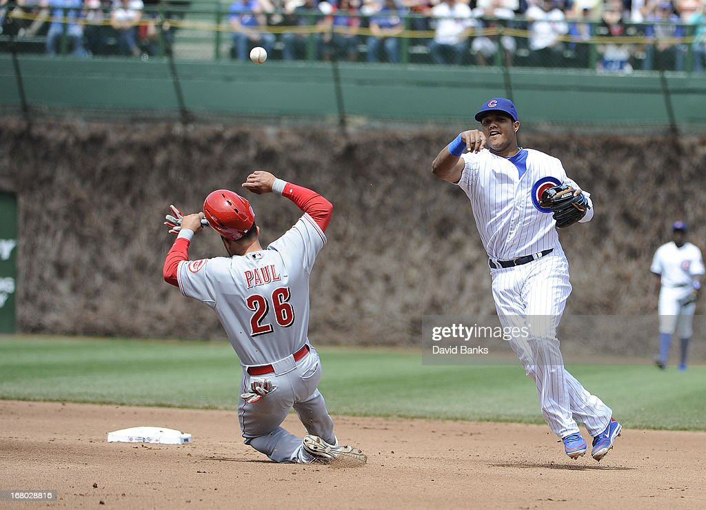 Starlin Castro #13 of the Chicago Cubs forces out Xavier Paul #26 of the Cincinnati Reds during the fourth inning on May 4, 2013 at Wrigley Field in Chicago, Illinois.
