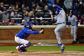 Starlin Castro of the Chicago Cubs gets tagged out at home plate by Travis d'Arnaud of the New York Mets after a single hit by Javier Baez of the...