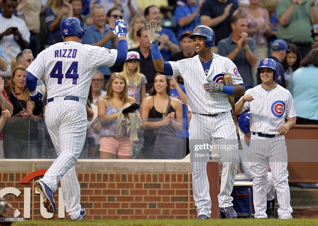 Starlin Castro #13 of the Chicago Cubs high-fives teammate Anthony Rizzo #44 after Rizzo hit a two-run home run scoring Javier Baez during the first inning against the San Francisco Giants at Wrigley Field on August 19, 2014 in Chicago, Illinois.