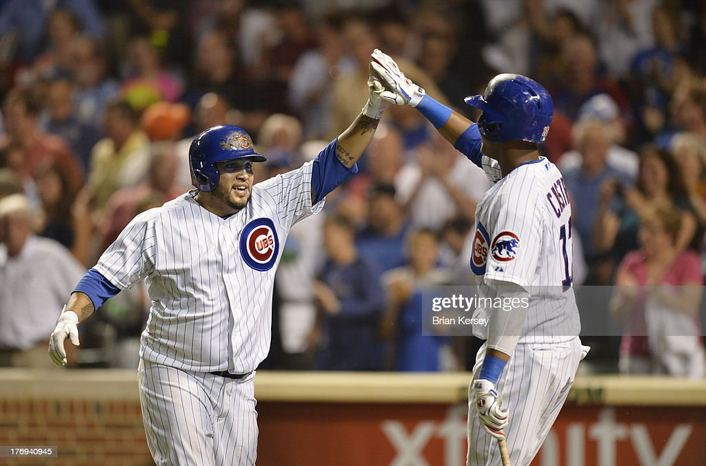 <a gi-track='captionPersonalityLinkClicked' href=/galleries/search?phrase=Starlin+Castro&family=editorial&specificpeople=5970945 ng-click='$event.stopPropagation()'>Starlin Castro</a> #13 of the Chicago Cubs (R) high-fives teammate <a gi-track='captionPersonalityLinkClicked' href=/galleries/search?phrase=Dioner+Navarro&family=editorial&specificpeople=593062 ng-click='$event.stopPropagation()'>Dioner Navarro</a> #30 after Navarro hit a three-run home run scoring Darwin Barney #15 and Junior Lake #21 during the fifth inning against the Washington Nationals at Wrigley Field on August 19, 2013 in Chicago, Illinois.