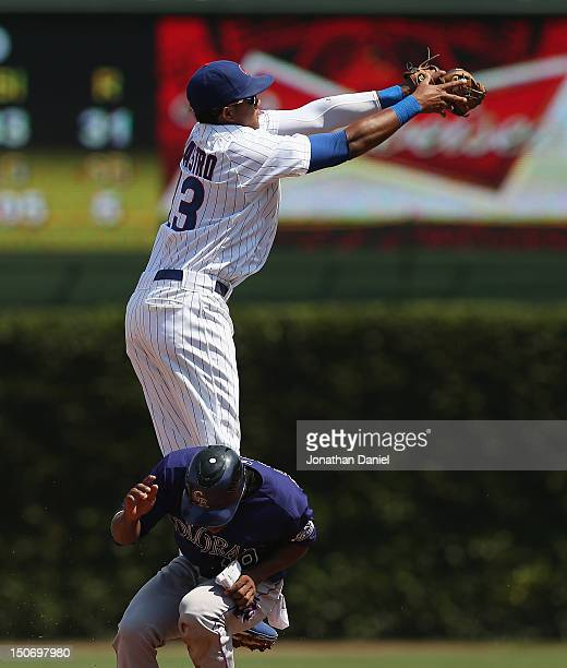 Starlin Castro of the Chicago Cubs leaps over Jonathan Herrera of the Colorado Rockies to make a catch at Wrigley Field on August 24 2012 in Chicago...