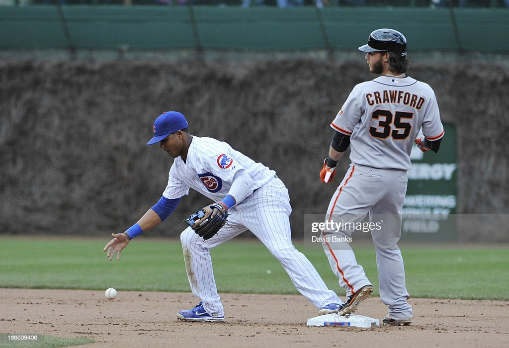 <a gi-track='captionPersonalityLinkClicked' href=/galleries/search?phrase=Starlin+Castro&family=editorial&specificpeople=5970945 ng-click='$event.stopPropagation()'>Starlin Castro</a> #13 of the Chicago Cubs makes an error as <a gi-track='captionPersonalityLinkClicked' href=/galleries/search?phrase=Brandon+Crawford&family=editorial&specificpeople=5580312 ng-click='$event.stopPropagation()'>Brandon Crawford</a> #35 of the San Francisco Giants is safe at second base during the seventh inning on April 13, 2013 at Wrigley Field in Chicago, Illinois.