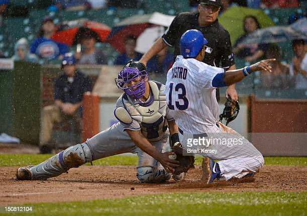 Starlin Castro of the Chicago Cubs scores on a sacrifice fly hit by teammate Joe Mather as catcher Wilin Rosario of the Colorado Rockies drops the...