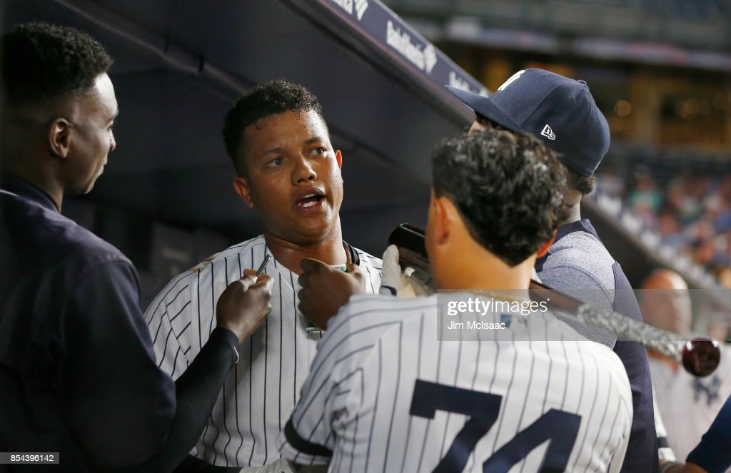 Starlin Castro #14 of the New York Yankees celebrates his second inning home run against the Tampa Bay Rays by granting an 'interview' to teammates Didi Gregorius #18 (L), Ronald Torreyes #74 and Luis Severino #40 at Yankee Stadium on September 26, 2017 in the Bronx borough of New York City.