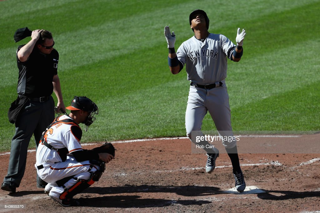 Starlin Castro #14 of the New York Yankees celebrates in front of catcher Caleb Joseph #36 of the Baltimore Orioles and home plate umpire Sean Barber #29 after hitting a sixth inning solo home run at Oriole Park at Camden Yards on September 7, 2017 in Baltimore, Maryland.