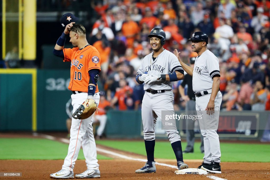 Starlin Castro #14 of the New York Yankees celebrates with first base coach Tony Pena #56 after his single in the fourth inning against the Houston Astros during game one of the American League Championship Series at Minute Maid Park on October 13, 2017 in Houston, Texas.