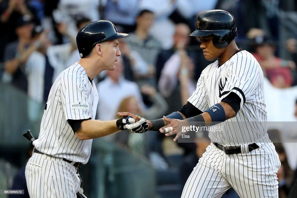 Starlin Castro #14 of the New York Yankees celebrates with Todd Frazier #29 after scoring on a Greg Bird #33 single during the second inning against the Houston Astros in Game Five of the American League Championship Series at Yankee Stadium on October 18, 2017 in the Bronx borough of New York City.