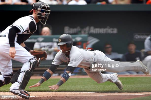 Starlin Castro of the New York Yankees scores against Caleb Joseph of the Baltimore Orioles off of a Aaron Hicks of the New York Yankees sacrifice...