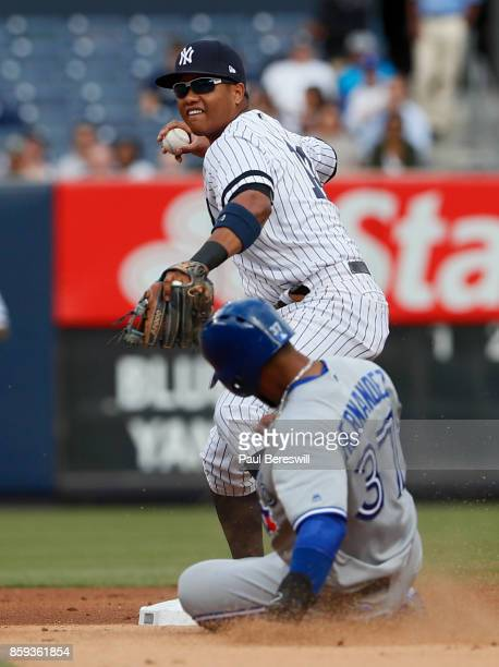 Starlin Castro of the New York Yankees throws to first to complete a double play in an MLB baseball game against the Toronto Blue Jays on September...