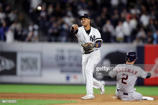 Starlin Castro of the New York Yankees throws to first to complete a double play and end the game during the ninth inning against the Houston Astros...