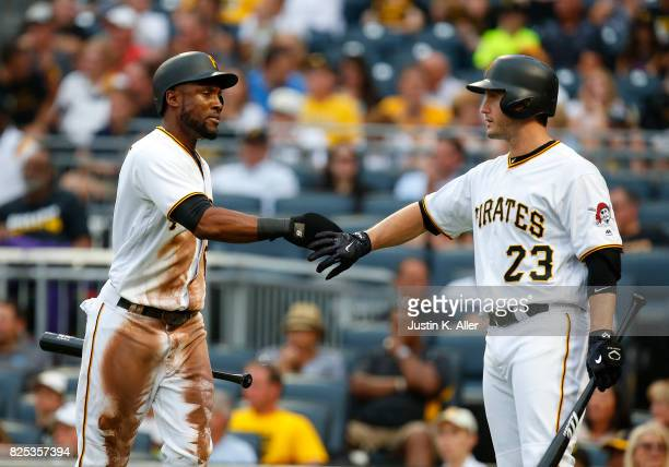 Starling Marte of the Pittsburgh Pirates celebrates with David Freese of the Pittsburgh Pirates after scoring on a RBI single in the first inning...
