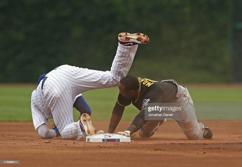 <a gi-track='captionPersonalityLinkClicked' href=/galleries/search?phrase=Starling+Marte&family=editorial&specificpeople=7934200 ng-click='$event.stopPropagation()'>Starling Marte</a> #6 of the Pittsburgh Pirates collides with <a gi-track='captionPersonalityLinkClicked' href=/galleries/search?phrase=Starlin+Castro&family=editorial&specificpeople=5970945 ng-click='$event.stopPropagation()'>Starlin Castro</a> #13 of the Chicago Cubs while stealing second base at Wrigley Field on July 6, 2013 in Chicago, Illinois.
