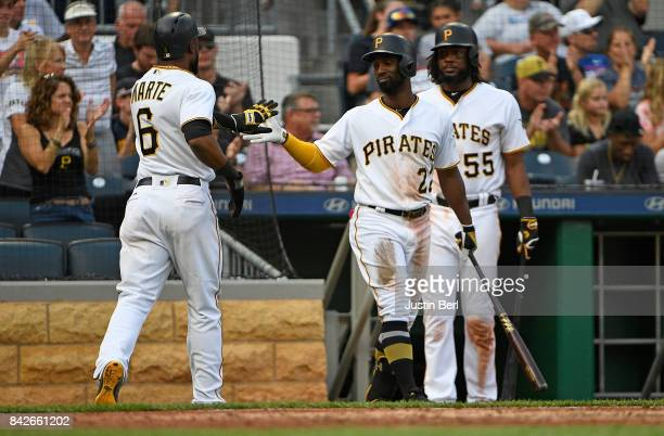 Starling Marte of the Pittsburgh Pirates is greeted by Andrew McCutchen after coming around to score on a RBI double by Max Moroff in the seventh...