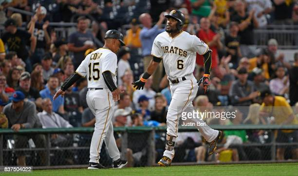 Starling Marte of the Pittsburgh Pirates is greeted by third base coach Joey Cora as he rounds third base after hitting a two run home run in the...