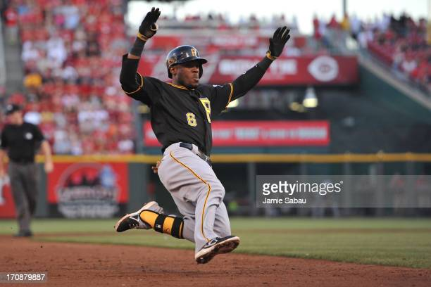 Starling Marte of the Pittsburgh Pirates slides in safely at third base for a triple in the third inning against the Cincinnati Reds at Great...