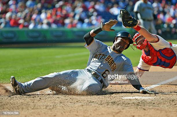 Starling Marte of the Pittsburgh Pirates slides safely into home past Erik Kratz of the Philadelphia Phillies in the eighth inning at Citizens Bank...