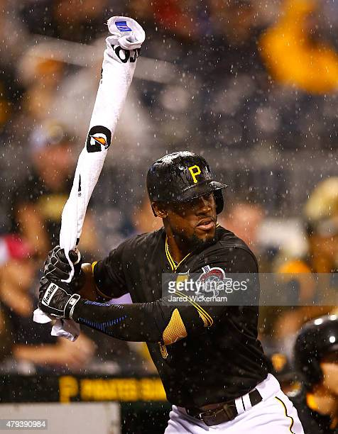 Starling Marte of the Pittsburgh Pirates warms up in the on deck circle with his bat covered in a Gatorade towel as the rain falls in the seventh...