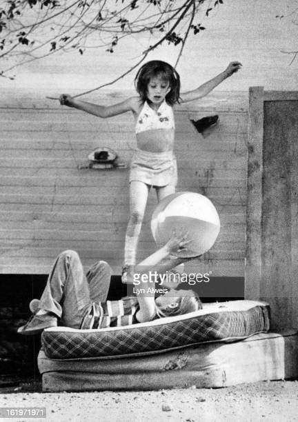 BALL Starr Groblebe with the ball and her sister Dawn use discarded mattresses as a trampoline as they enjoy Wednesday's warm spring weather...