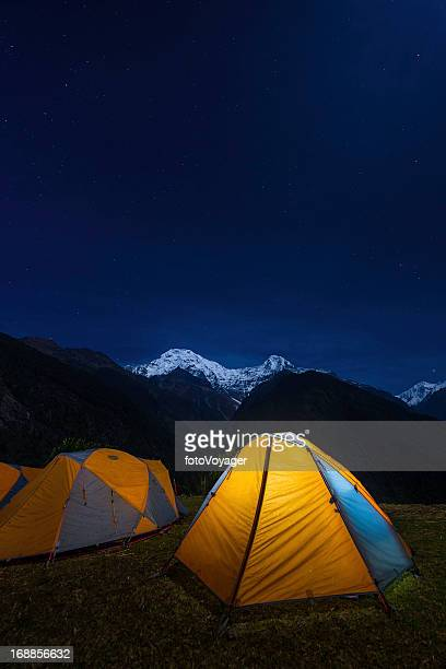 Starry skies above snowy mountains and yellow tent base camp