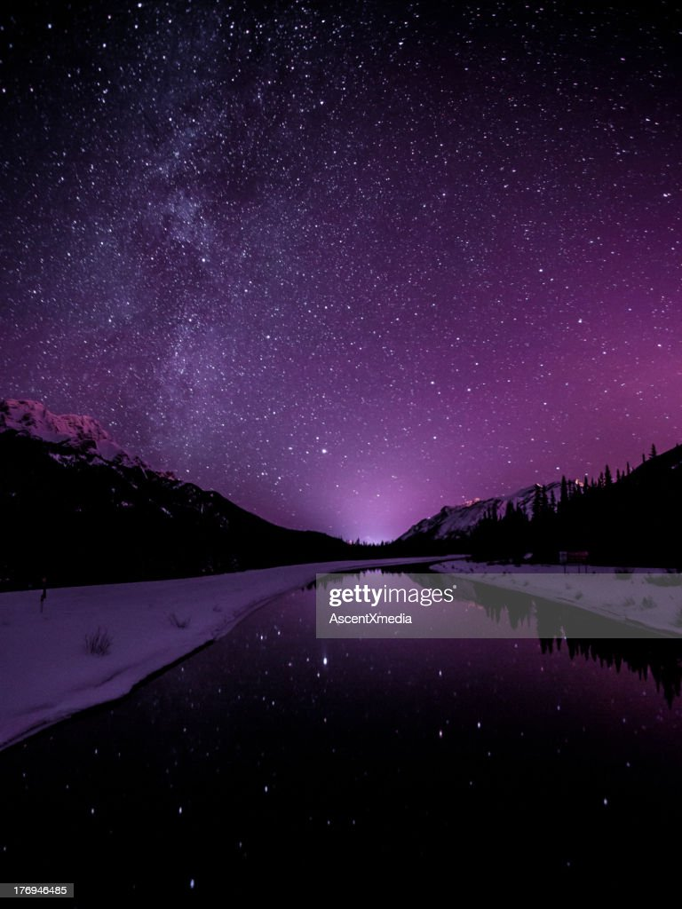 Starry sky illuminates mountain landscape : Stock Photo