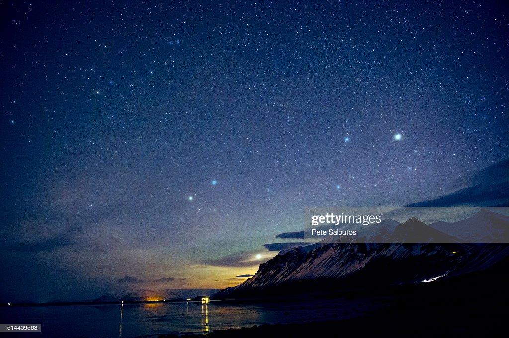 Starry sky over still ocean in arctic landscape