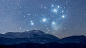 This is a combination of two photos taken separately, one of a mountain range, the other of Pleiades. Pleiades are out of proportion and the idea is to depict how it would look if the Deep Space Objec