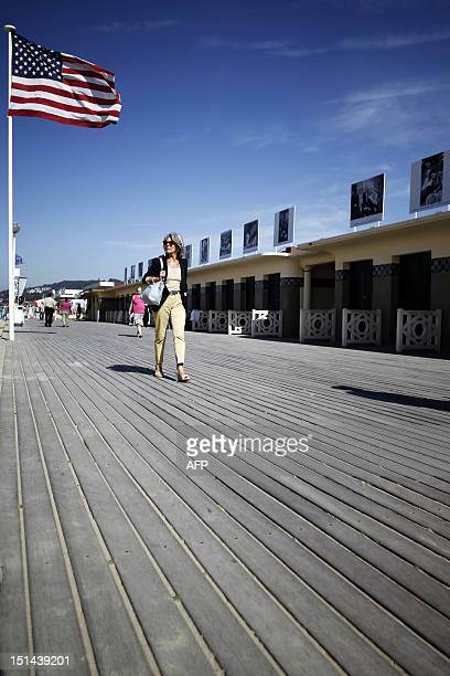 A US stars and stripes flag waves while a woman is walking along the Promenade des Planches on September 7 in the French northwestern sea resort of...
