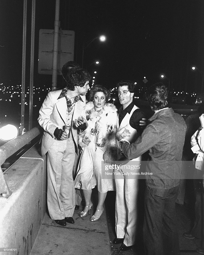 Stars Joe Cali (left), Donna Pescow and John Travolta (2nd right) on the set of the movie 'Saturday Night Fever.' Part of the Verrazano Bridge was closed for movie making of 'Saturday Night Fever' which is based on a New York magazine article. Travolta and buddies are coming home Saturday night from a Brooklyn disco and stop on bridge to wind down. Suddenly it all becomes a macho scene with lots of showing off, like handstands on bridge rails and then there is a tragic climax at scene.,