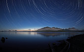 Stars shine brightly over Kennedy Lake near the central west coast of Vancouver Island in British Columbia, Canada. The lake is a short distance away from the tourist destination of Tofino. The lake i