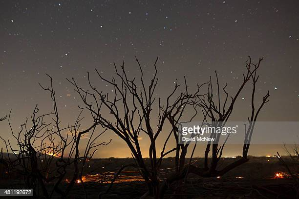Stars shine over a landscape of embers burning in the wake of the North Fire which caused people to abandon their vehicles and flee as flames jumped...