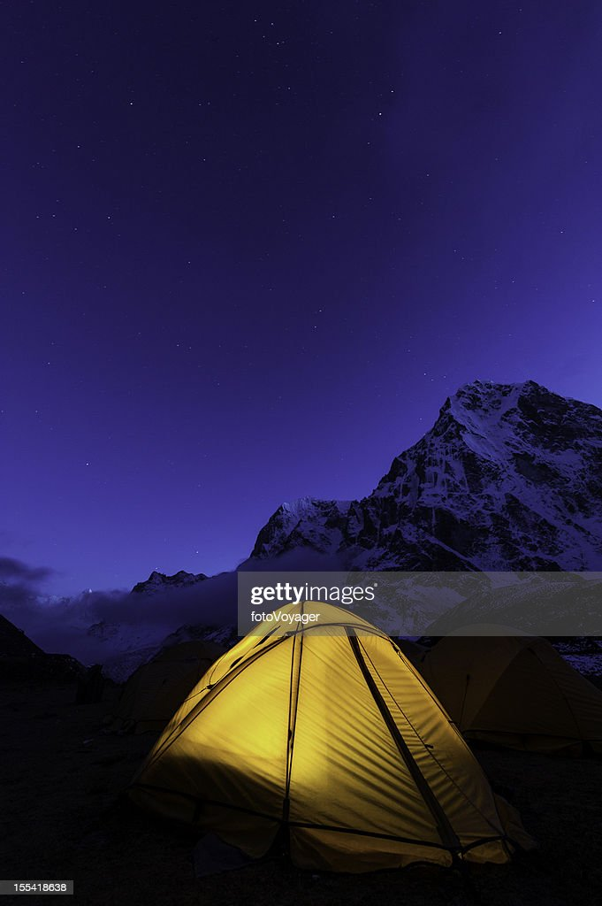 Stars shining bright above yellow mountain tent