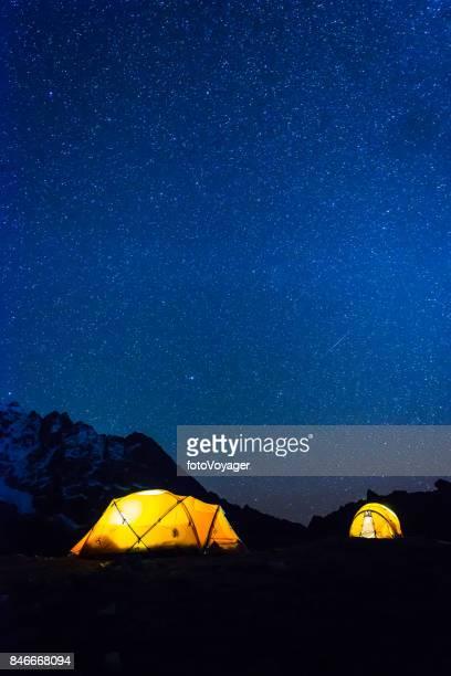 Stars shining night sky over illuminated mountain tents Himalayas Nepal