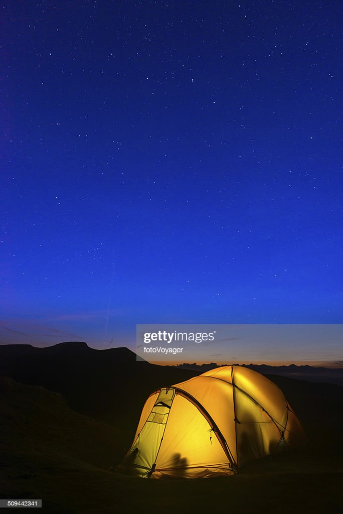 Stars shining over warm glowing tent and silhouetted mountain peaks