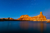 Long exposure shot of the landscape of Lake Powell and the cosmos spinning above