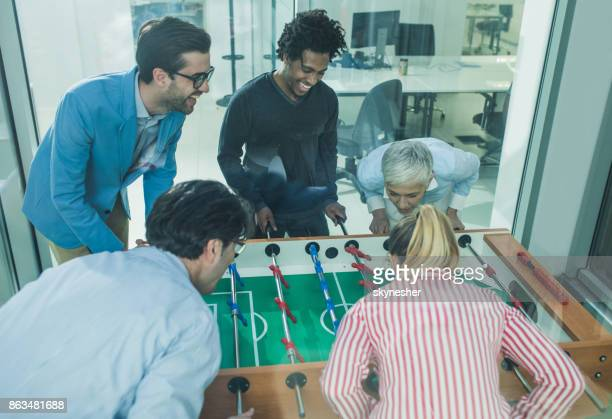 Start up team having fun while playing table soccer on a break.