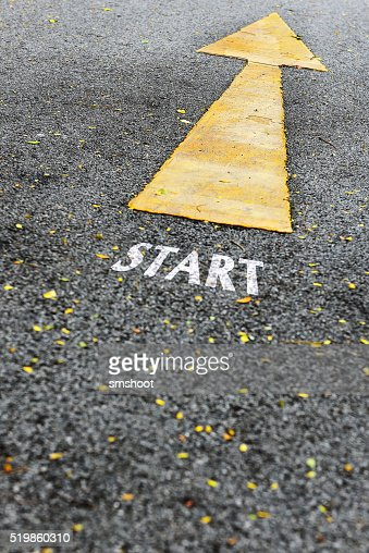Start word and single yellow arrow sign marking on road : Stock Photo